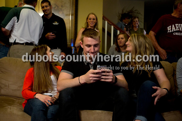 Ariana van den Akker/The Herald Ben Braunecker of Ferdinand, center, hung up the phone after receiving a free agent offer while watching the NFL draft at home on Saturday surrounded by family and friends including his mother Kristine Braunecker of Ferdinand, right, and his girlfriend Maria Kalina of Cambridge, Mass. Braunecker signed with the Chicago Bears Saturday night as an undrafted free agent.