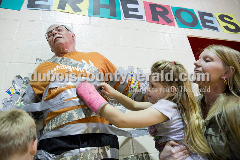 Sarah Ann Jump/The Herald<br /> Holland Elementary kindergartener Lilly Houchins, lifted by her teacher Jessica Niehaus, applied a piece of duct tape to principal Al Mihajlovits in hopes of taping him to the wall during the school's Riley Day celebration on Friday.