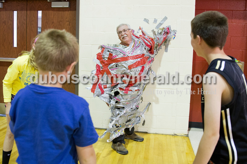 Sarah Ann Jump/The Herald<br /> Principal Al Mihajlovits fell shortly after the stools were pulled from beneath him, despite all of the tape applied by students, during Holland Elementary's Riley Day celebration on Friday. For a $1 donation, students were each given an arms length of tape.