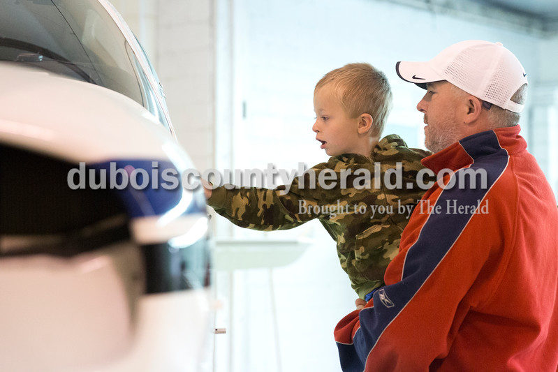 Sarah Ann Jump/The Herald<br /> Philip Beck of Jasper held up his son Ethan, 2, to see inside an airplane during the Radio Control Aviation Appreciation Fly In at Huntingburg Airport on Saturday.