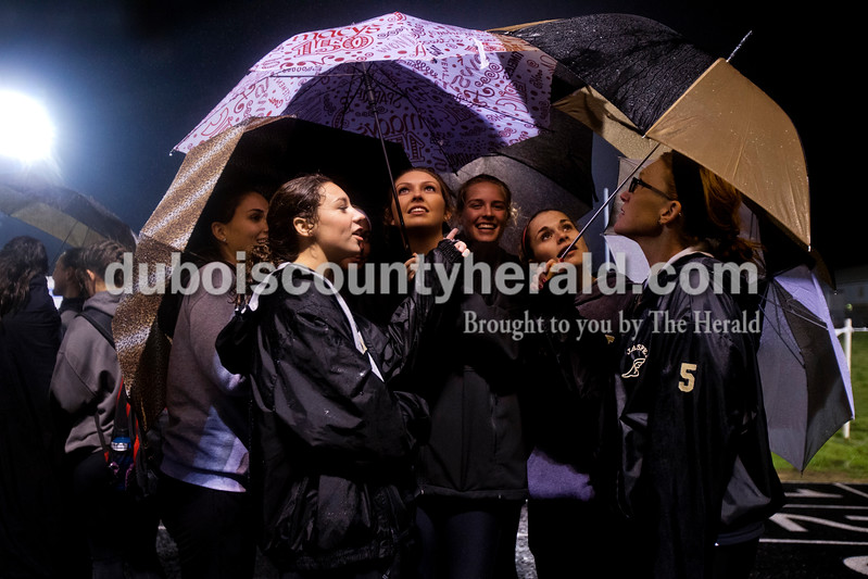 Jasper's Hannah Love, Annie Stout, Chloe Berger, Kirby Ruhe, Reagan Otto and coach Erin Spellmeyer took shelter under umbrellas as they huddled together to wait for final scores after Tuesday's IHSAA girls track sectional at Perry Central. Jasper took first place in the 10-team meet.<br /> <br /> Alisha Jucevic/The Herald