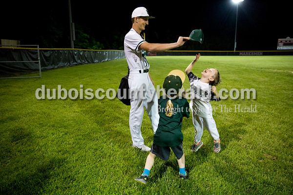 Forest Park's Braydon Voegerl held up the hat of Kody Greulich, 4, son of coach Kyle Greulich, as he jumped for it with Bree Howard, 5, daughter of coach Jarred Howard, after Wednesday's Class 2A sectional in Tell City. The Forest Park Rangers defeated the Evansville Mater Dei Wildcats 10-0 in five innings. Sarah Ann Jump/The Herald