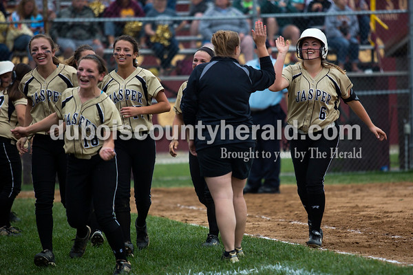 Jasper coach Jennifer Bartley high-fived Olivia Knies, right, after Knies made a home run in the sixth inning of Thursday night's Class 3A sectional championship against Pike Central in Petersburg. The Wildcats secured a 3-0 win and will move on to play Boonville in the regional championship on Tuesday at the Jasper Youth Sports Complex.  Alisha Jucevic/The Herald