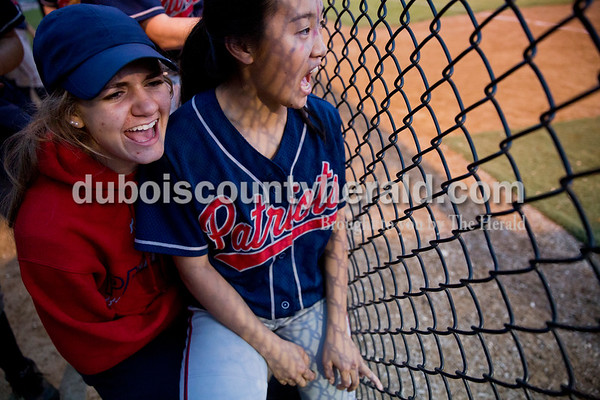 Heritage Hills' Morgan Vaal and Xiana Scott shared a bucket and cheered from the dug out during Thursday's Class 3A sectional championship game in Boonville. The Heritage Hills Patriots lost to the Boonville Pioneers 8-2. Sarah Ann Jump/The Herald