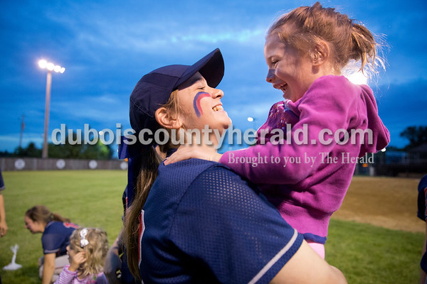 Heritage Hills' Claire Brinkman held Charlotte Asbury, 5, daughter of head coach Joe Asbury, after Thursday's Class 3A sectional championship game in Boonville. The Heritage Hills Patriots lost to the Boonville Pioneers 8-2. Sarah Ann Jump/The Herald