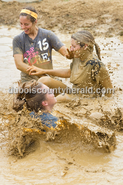 Sarah Ann Jump/The Herald Jasper High School seniors Hanna Braunecker, back left, Reagan Hochmeister and Rachael Welsh, front, played in the mud during the school's annual mud volleyball tournament on Wednesday.