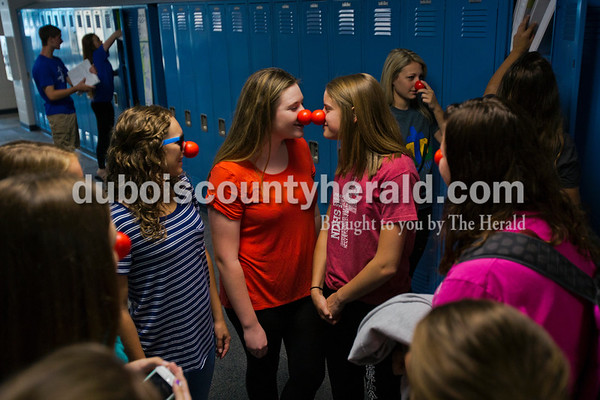 Alisha Jucevic/The Herald   Northeast Dubois High School freshman Sierra Jones, left, and Molly Lueken poked their red noses together as students gathered in the hallways to clean out lockers on Thursday morning in Dubois. Northeast Dubois teacher Karen Terwiske and the Beta Club led the efforts to sell around 200 noses to students during their homeroom period to support Red Nose Day. This national campaign brings people together with comedy to raise money for children and young adults living in poverty.