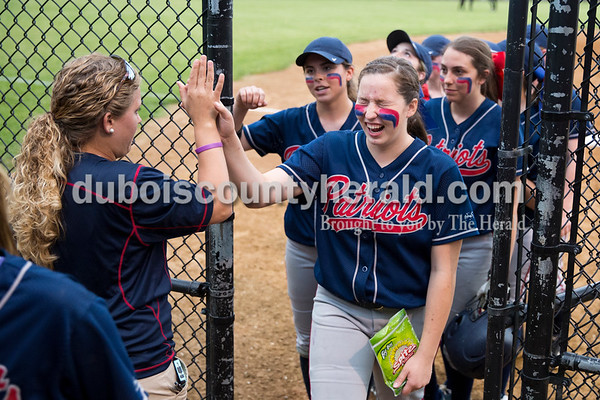 Heritage Hills' Whitney Ward laughed as she high fived assistant coach Katara Luebbehusen after an inning during Thursday's Class 3A sectional championship game in Boonville. The Heritage Hills Patriots lost to the Boonville Pioneers 8-2. Sarah Ann Jump/The Herald