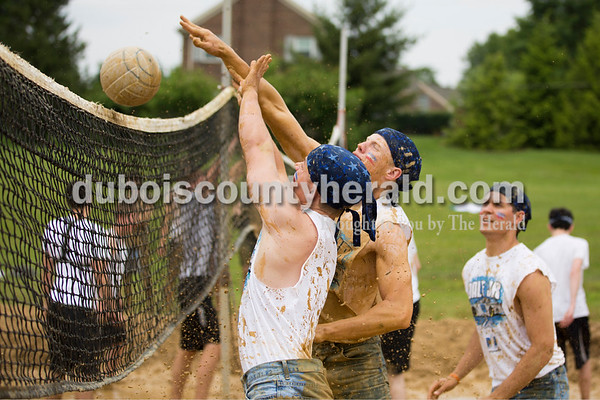 Sarah Ann Jump/The Herald Jasper High School seniors Ben Wendholt, left, and Tate Blessinger hit the ball over the net during the school's annual mud volleyball tournament on Wednesday. Their team won the tournament.