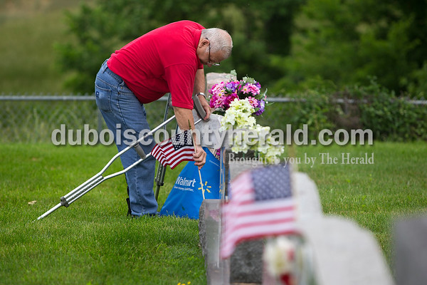 Dave Weatherwax/The Herald Despite being hobbled by a broken left ankle and crutches, Sylvan May of Possum Junction spent Saturday morning finishing the task of planting 144 American flags in front of the tombstones of the veterans who rest in St. Meinrad Cemetery. May, a U.S. Army veteran of the Vietnam War, has carried out the task every year for Memorial Day for the past 30 Years.