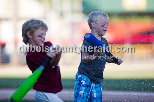 Tanner Hall of French Lick, 7, left, and Brayden Kratzer of Jasper, 7, swung at water ballons in between innings of Friday night's game between the Dubois County Bombers and the Owensboro Oilers at League Stadium in Huntingburg. The Bombers won 6-2.  Alisha Jucevic/The Herald
