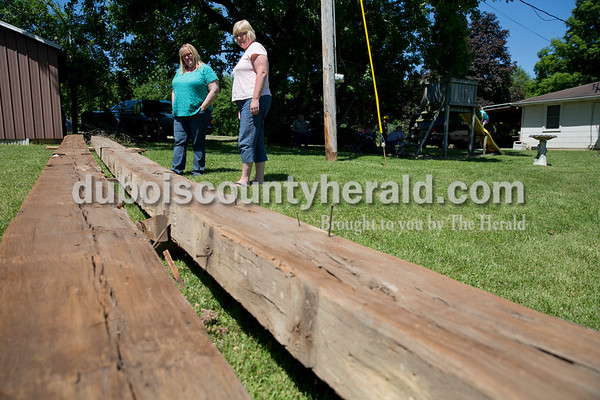 Sarah Ann Jump/The Herald Staci Bolden, left, and her cousin Lisa Huff, both of Birdseye, checked out two beams removed from Bolden's barn during filming for the DIY Network show Barnwood Builders in Birdseye on Wednesday, June 8.