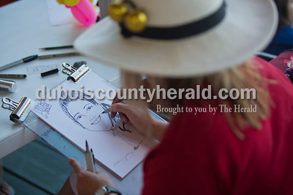Karen Kovich of Bloomington, aka The Hoosier Queen of Caricature, drew black and white caricatures for $2 a piece during Friday night's game between the Dubois County Bombers and the Owensboro Oilers at League Stadium in Huntingburg. The Bombers won 6-2.  Alisha Jucevic/The Herald
