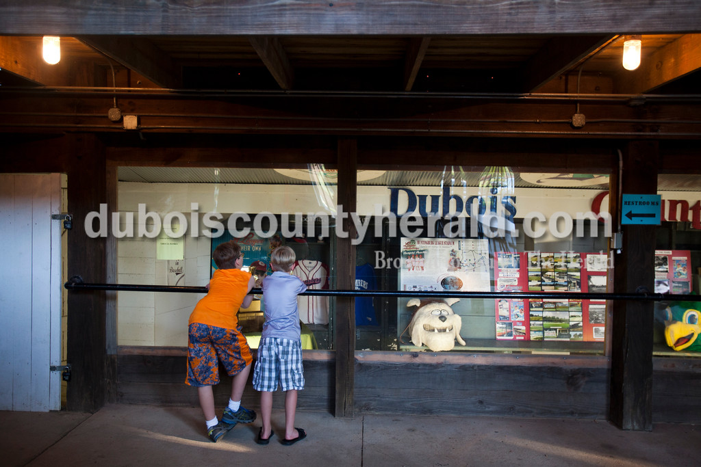 """Ben Ludlow, 11, and his brother Noah, 9, both of Santa Claus, looked at the """"League of their Own"""" museum window underneath the stadium during Friday night's game between the Dubois County Bombers and the Owensboro Oilers at League Stadium in Huntingburg. The Bombers won 6-2. <br /> Alisha Jucevic/The Herald"""