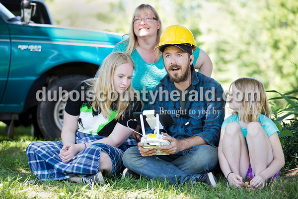 Sarah Ann Jump/The Herald Director Travis Tips of Brooklyn, NY sat with property owner Staci Bolden of Birdseye and her daughters Serena Kelly, 17, left, and Marissa Bolden, 7, as he flew a drone to film during a barn deconstruction for the DIY Network show Barnwood Builders in Birdseye on Wednesday, June 8. With a live stream of the footage from the drone, he showed them an aerial view of where they used to jump in the hay piles in the barn.