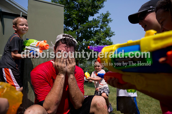 """Sarah Ann Jump/The Herald Dubois County Bombers player Zack Gray of Hamilton, Ohio shielded his face as he was surrounded by children with water guns, including Patrick Verkamp of Schnellville, 7, left, during Water Wars, a squirt gun fight against members of the Dubois County Bombers and Rockford Peaches, at the Ferdinand Public Library on Tuesday. """"We want to make a positive impact on the community,"""" said Dubois County Bombers shortstop Ben Balgaard of Fenton, Mich. """"My favorite part is seeing the smiles on the kids' faces. We want to give them something to remember."""""""