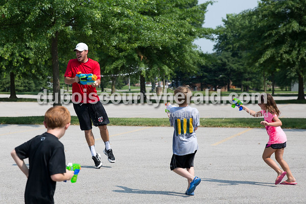 Sarah Ann Jump/The Herald Dubois County Bombers player Zack Gray of Hamilton, Ohio was chased by Augie Simmers of Jasper, 6, left, John DeWitte of Kyana, 8, and Nora Breitwieser of Jasper, 7, against during Water Wars at the Ferdinand Public Library on Tuesday.