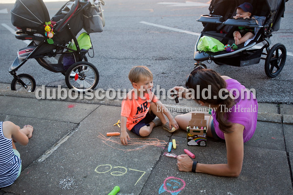 Megan Brinkman of St. Anthony picked out chalk with her son Leo, 3, during Saturday's 13th annual Jasper Arts Center Chalk Walk around the Courthouse Square in downtown Jasper.  Alisha Jucevic/The Herald