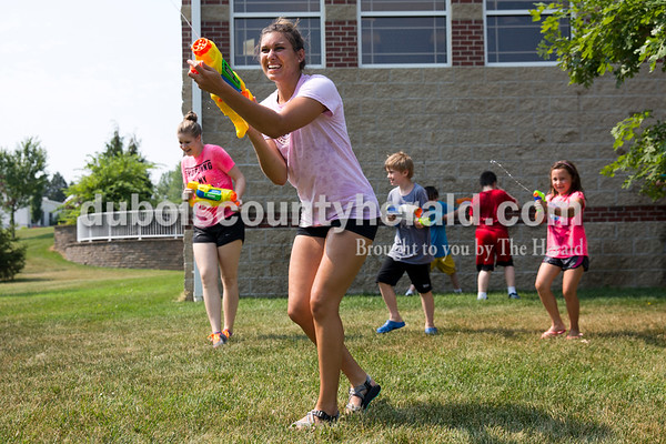 Sarah Ann Jump/The Herald Rockford Peach Jaclyn Altstadt of Huntingburg fired her water gun as Nora Breitwieser of Jasper, 7, right, squirted her from behind during Water Wars at the Ferdinand Public Library on Tuesday.