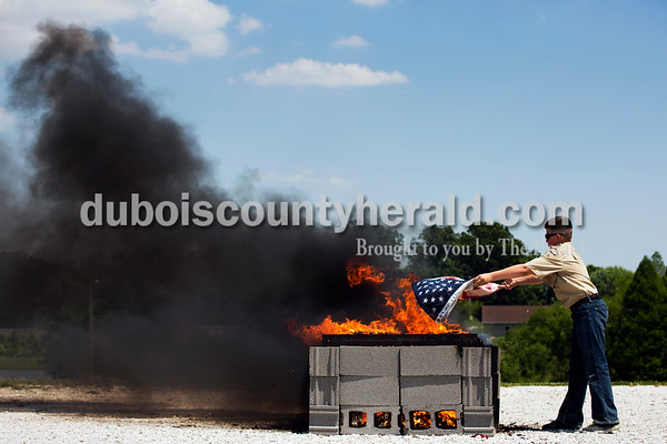 Sarah Ann Jump/The Herald Boy Scout Jackson Smith of Huntingburg, 11, placed a retired American flag on the burn pit during the Dubois County Veterans Council's annual flag disposable ceremony at the 4-H Fairgrounds in Bretzville on Saturday afternoon.