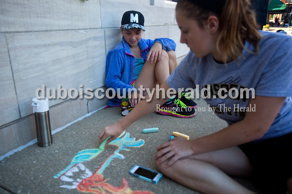 Concrete squares were filled with color on Saturday for the 13th annual Jasper Arts Center Chalk Walk around the Courthouse Square in downtown Jasper. Maggie Sternberg of Jasper, 10, watched her sister Clara, 13, draw a dragon. Clara said she loves to draw and she chose a dragon for today's event because wanted to challenge herself.  Alisha Jucevic/The Herald