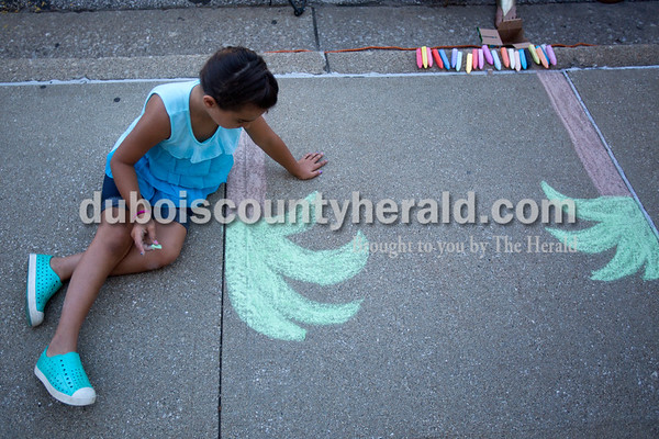 Concrete squares were filled with color on Saturday for the 13th annual Jasper Arts Center Chalk Walk around the Courthouse Square in downtown Jasper. Lisa Seger of Jasper, 7, began working on her square, drawing a rainforest with two large trees on the sides of her square.  Alisha Jucevic/The Herald
