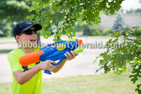 Sarah Ann Jump/The Herald Levi Gayso of Ferdinand, 10, hid behind a tree to shoot during Water Wars at the Ferdinand Public Library on Tuesday.