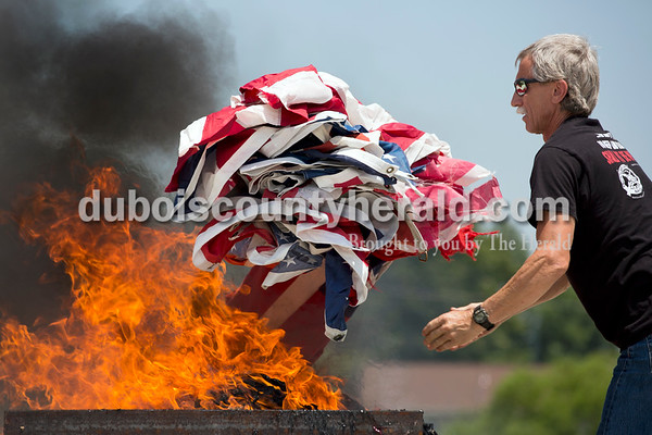Sarah Ann Jump/The Herald Randy Niehaus of Huntingburg threw a stack of flags on the fire during the Dubois County Veterans Council's annual flag disposable ceremony at the 4-H Fairgrounds in Bretzville on Saturday afternoon.