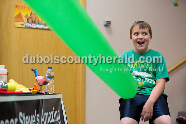 Sarah Ann Jump/The Herald Reuben Harker of Jasper, 10, reacted as Steve Walden instantaneously inflated a long cylindrical plastic bag during Professor Steve's Science of Basketball Show at the Jasper Public Library on Tuesday afternoon.