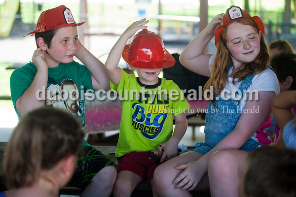 Alisha Jucevic/The Herald   Corvin Hoffman of Mentor, 8, Matt Kern of Birdseye, 7, and Riley Setser of Eckerty, 9, adjusted their new fire helmets after a fire and safety class with firefighter Jeff Owens and his service dogs on Thursday afternoon put on by the Birdseye Branch Library in the Birdseye City Park. After the program, the Birdseye Volunteer Fire Department handed out fire helmets to the children and let them take photos with their fire truck.