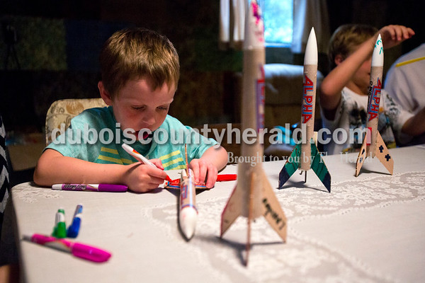 Alisha Jucevic/The Herald   Landon Small of Huntingburg, 4, decorated a rocket on Wednesday evening at his great-grandparent's home, Jim and Clara Vaal, in Ferdinand.