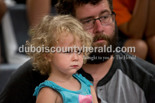 Sarah Ann Jump/The Herald Crosby Mitchell of Jasper, 2, watched intently with her father Eric as Steve Walden lit a fire during Professor Steve's Science of Basketball Show at the Jasper Public Library on Tuesday afternoon.