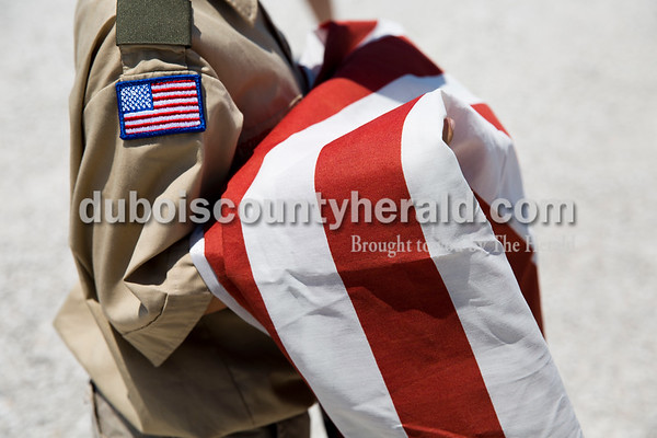 Sarah Ann Jump/The Herald Boy Scout Devon Osborn of St. Anthony, 11, held a flag to be burned during the Dubois County Veterans Council's annual flag disposable ceremony at the 4-H Fairgrounds in Bretzville on Saturday afternoon.