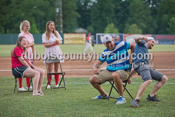 Chris Kunz of St. Anthony, second from right, edged Cole Schneider of Huntingburg off a chair to claim victory in a musical chairs contest between innings during Tuesday evening's game between the Dubois County Bombers and Paducah Chiefs at League Stadium in Huntingburg. Rockford Peaches Sienna Crews of Lincoln City, left, and Joyce Lawrence of Huntingburg watched along with contestant Katyn Vierman of Greenville. The Bombers won 4-2. Sarah Ann Jump/The Herald