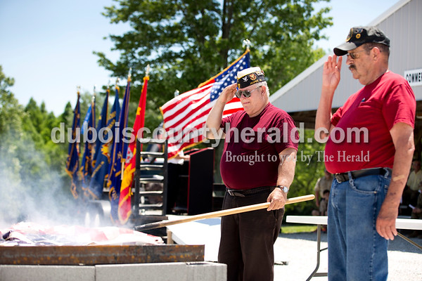 Sarah Ann Jump/The Herald Jasper Navy Club secretary Bernie Thewes of Portersville, left, and Jasper American Legion Post 147 Commander Bob Bleemel of Hillham saluted as the first flags were burned during the Dubois County Veterans Council's annual flag disposable ceremony at the 4-H Fairgrounds in Bretzville on Saturday afternoon.