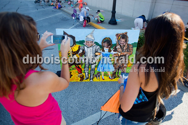 Karen Legris, left, and Summer Stubbs, both of Jasper, took photos of their sons Elijah Stubbs, 4, Ryan Legris, 3, Evan Legris, 4, and Liam Stubbs, 2, as they played behind a Wizard of Oz cut out during Saturday's 13th annual Jasper Arts Center Chalk Walk around the Courthouse Square in downtown Jasper  Alisha Jucevic/The Herald