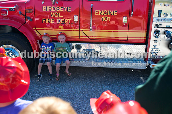 Alisha Jucevic/The Herald   Owen Madden, 3, and his brother Cameron, 5, both of Birdseye looked toward their aunt for a photo after The Kasey Program on Thursday afternoon put on by the Birdseye Branch Library in the Birdseye City Park. After the program, the Birdseye Volunteer Fire Department handed out fire helmets to the children and let them take photos with their fire truck.