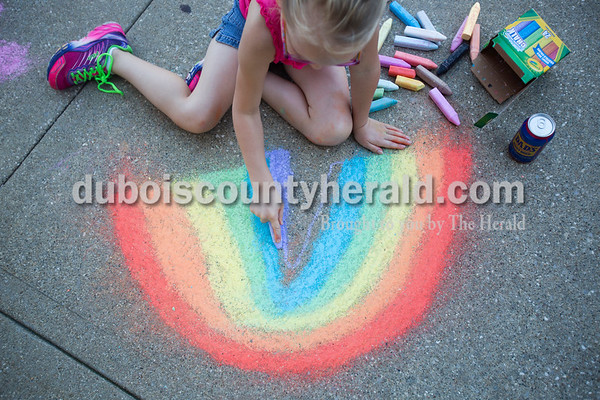 Concrete squares were filled with color on Saturday for the 13th annual Jasper Arts Center Chalk Walk around the Courthouse Square in downtown Jasper. Alayna Schnell of Schnellville, 6, smoothed out the purple layer of her rainbow during the event.  Alisha Jucevic/The Herald