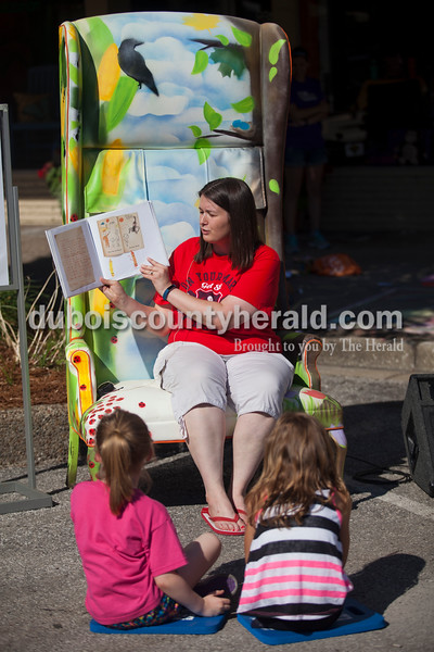 """Jasper Library Director, Christine Golden of Holland, read a story to children in the """"Reader's Chair,"""" during Saturday's 13th annual Jasper Arts Center Chalk Walk around the Courthouse Square in downtown Jasper. The chair was designed by artist Emily Kennerk and made possible by a partnership between Arts for Learning and Indiana Furniture.  Alisha Jucevic/The Herald"""