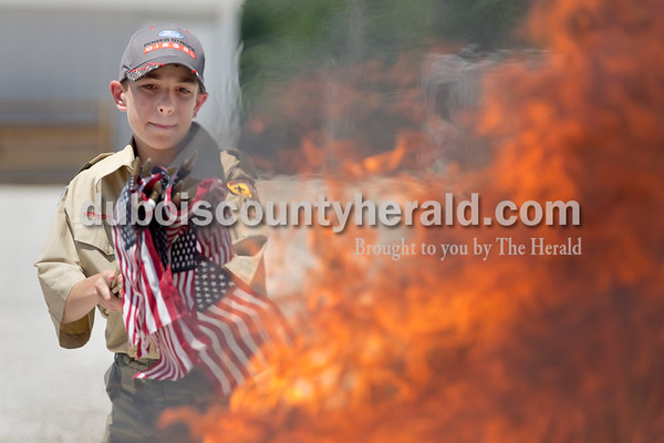 Sarah Ann Jump/The Herald Boy Scout Brent Wissel of Huntingburg, 11, threw a handful of small flags on the fire during the Dubois County Veterans Council's annual flag disposable ceremony at the 4-H Fairgrounds in Bretzville on Saturday afternoon.