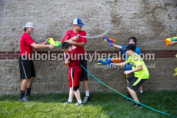 Sarah Ann Jump/The Herald Dubois County Bombers players Ian Dimitrie of Madison Heights, Mich., left, and Miles Hardy of Oakland, Mich., center, battled against Templar Werne of Dale, 9, center, Levi Gayso of Ferdinand, 10, and Malachi Werne of Dale, 11, during Water Wars at the Ferdinand Public Library on Tuesday.