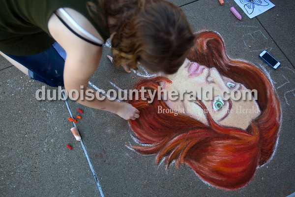 Cosette Fehribach of Ferdinand, 19, worked on her drawing during Saturday's 13th annual Jasper Arts Center Chalk Walk around the Courthouse Square in downtown Jasper. Alisha Jucevic/The Herald