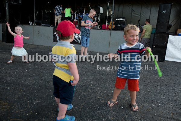 Sarah Ann Jump/The Herald Emma Schmitt of Jasper, 2, left, Beau Erny of Holland, 2, Drew Harpenau of Huntingburg, 14, and Lane Erny of Holland, 3, danced to music playing as the local band Broken Silence took a break during Heinrichsdorf Fest in St. Henry on Friday evening.