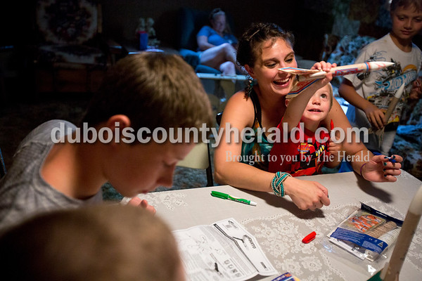 Alisha Jucevic/The Herald   Alysia Small and her son Bryson, 2, both of Huntingburg decorated a rocket together on Wednesday evening at Jim and Clara Vaal's house in Ferdinand. Jim and Clara are Alysia's grandparents and Bryson's great-grandparents. Alysia said she remembers watching the rockets as a child and it is special for her to see her two sons get to participate in the tradition and spend time with their great-grandfather. Jim was a science teacher for 33 years and loved to make rockets with his students in class as one of their projects. After retiring he continued to make them at home and during family get togethers he let the kids and grandchildren set them off into the air. This year, with great-grandchildren as well, the family decided to have the kids over to decorate the rockets in preparation for the August family picnic.