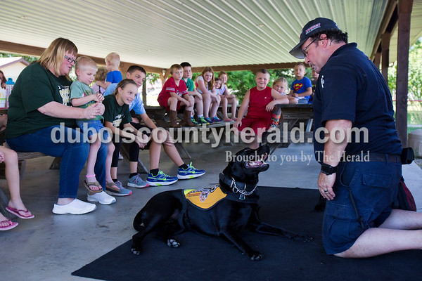 Alisha Jucevic/The Herald   Firefighter Jeff Owens led a fire and safety class with his service dogs on Thursday afternoon put on by the Birdseye Branch Library in the Birdseye City Park. Owens travels the country with his black Labrador Retrievers, taking an entertaining and fun approach to teaching fire and safety tips to children with The Kasey Program. The dogs help demonstrate skills like Stop, Drop & Roll, checking the door to see if it's hot and crawling under the smoke. Owens' dogs also wear the badge of the Indianapolis Fire Department and are trained as search and rescue as well as therapy dogs.