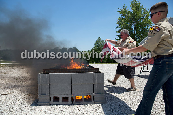 Sarah Ann Jump/The Herald Assistant Scout Master Alan Brenner of Jasper, left, and Boy Scout Jackson Smith of Huntingburg, 11, placed a large American flag on the burn pit during the Dubois County Veterans Council's annual flag disposable ceremony at the 4-H Fairgrounds in Bretzville on Saturday afternoon.