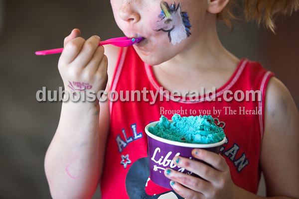 Taking a break from the hot sun and Jasper Community Arts Commission Chalk Walk last Saturday, Bailey Hagan of Jasper, 4, tasted a fresh scoop of Cookie Monster ice cream at Libby's. Matt said there is often a group waiting for the store to open during busy events on Courthouse Square like the Chalk Walk and Strassenfest. Alisha Jucevic/The Herald