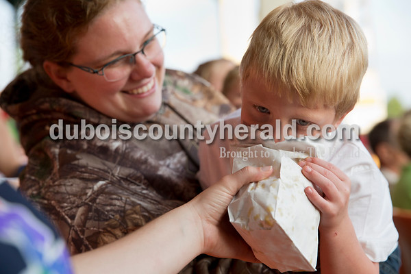 Nathaniel Inman of Jasper, 4, ate popcorn out of a bag held by his aunt Emily Cushman as his step-mother Melissa Cushman looked on and laughed during Tuesday evening's game between the Dubois County Bombers and Paducah Chiefs at League Stadium in Huntingburg. The Bombers won 4-2. Sarah Ann Jump/The Herald