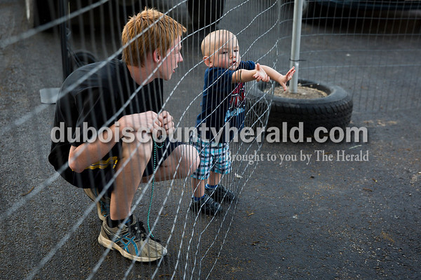 Sarah Ann Jump/The Herald Noah Love of Dubois, 15, watched as Gabriel Richardson of Loogootee, 1, reached through a fence during Heinrichsdorf Fest in St. Henry on Friday evening.