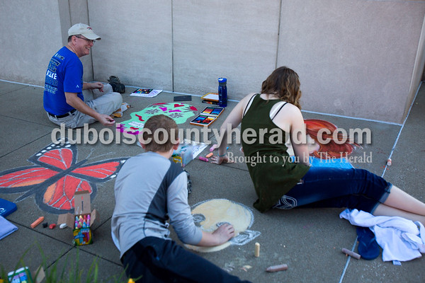 """Concrete squares were filled with color on Saturday for the 13th annual Jasper Arts Center Chalk Walk around the Courthouse Square in downtown Jasper. Brett Fehribach of Ferdinand, back left, chatted with his children, Beckett, 13, center, Cosette, 19, right, and this wife, Renee, not pictured, as they worked on their squares together on Saturday morning. Brett said the family has participated in the Chalk Walk together for about 11 years. """"We all enjoy doing it so it's a good time to spend together,"""" he said.  Alisha Jucevic/The Herald"""